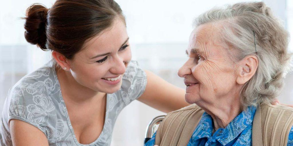 Une préposée d'aide à domicile sourit à une ainée